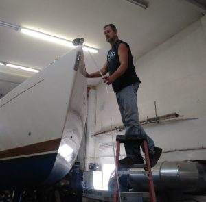 Bill the boat craftsman standing on a ladder inspecting a boat restoration process - JDOC Marine LLC