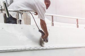 Craftsman polishing the new gelcoat finish on a boat - JDOC Marine LLC